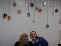 Two Junior Humanities students, Annie Maras and Carolyn Rutishauser, pose with masks made by the phase four class.