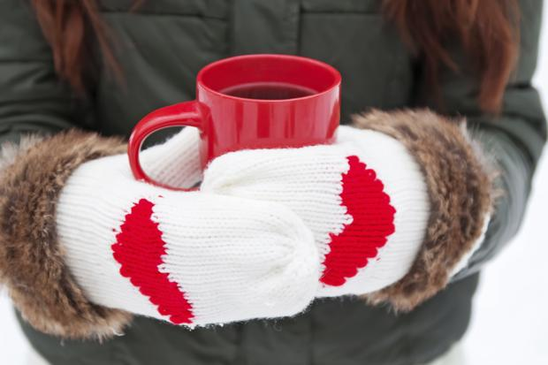 Hands in mittens with hearts holding cup