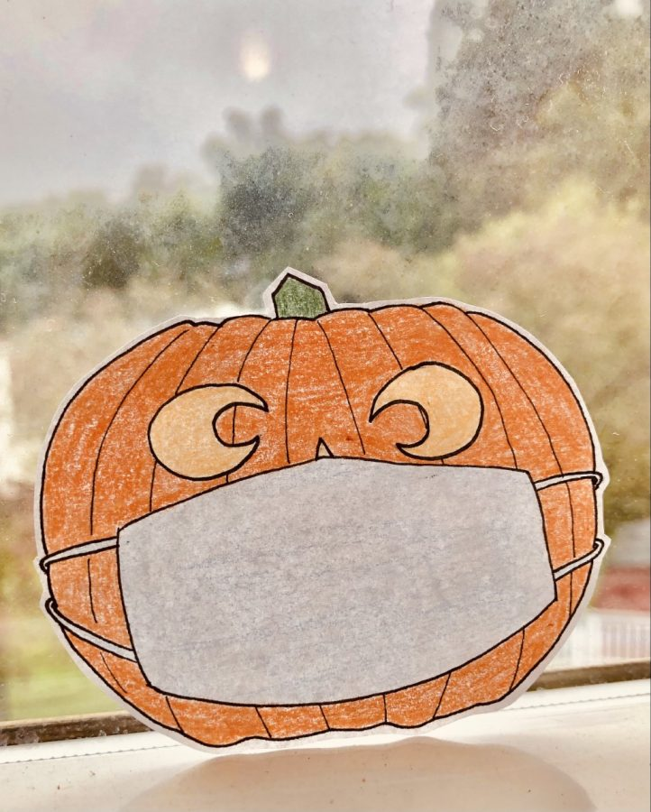 A masked pumpkin practices social distancing.